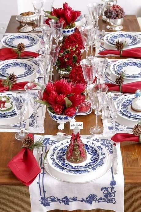 31. Decoração para mesa de natal com flores vermelhas e louças estampas azuis – Foto: Fashion Submarine