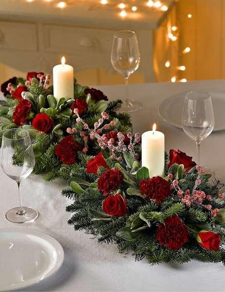 5. Decoração clássica com arranjos de mesa de natal com velas e flores vermelhas – Foto: Marks & Spencer