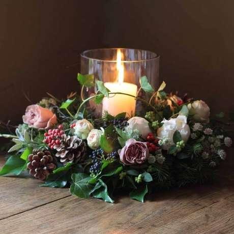 1. Arranjo de natal feito com folhagens, flores, pinhas e uma única vela no meio – Foto: Alaric Flowers