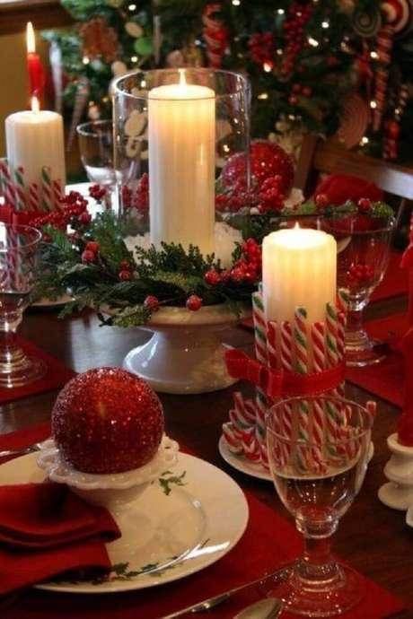 41. Decoração com arranjos de natal com velas e bolas vermelhas – Foto: Thiago Calil decor