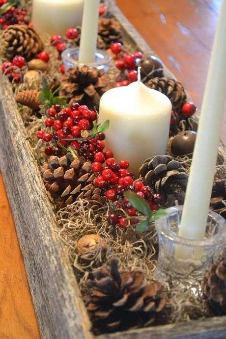 48. Arranjos de natal com velas e pinhas em suporte rústico de madeira – Foto: Leka Guimarães