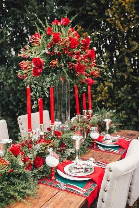 6. Linda decoração para ceia com arranjos de mesa de natal feitos com velas e rosas vermelhas – Foto: Style Me Pretty
