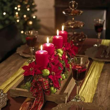 68. Suporte de madeira para arranjos de natal com velas e flores vermelhas – Foto: Pinterest