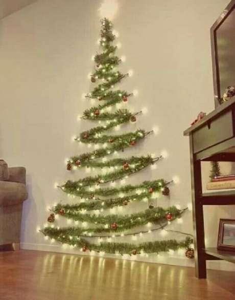 14. Se você mora em um apartamento pequeno é possível fazer um árvore de natal que não vai ocupar muito espaço, para isso você precisa de festão e luzes de natal – Foto: Her Campus