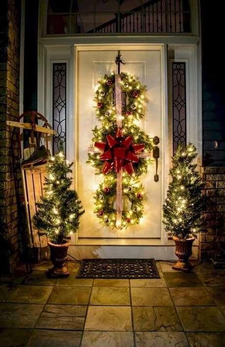 20. Linda decoração com luzes de natal para área externa decorada com dois pinheiros pequenos e guirlandas na porta – Foto: Roomodeling