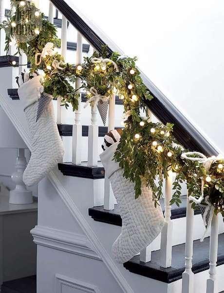 29. As luzes de natal são garantia de lindos arranjos decorativos para o corrimão da escada – Foto: The Grad