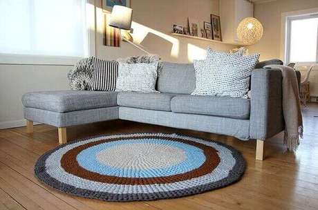 1- O tapete de crochê redondo em várias cores tem anel cinza combinando com a mesma cor do sofá. Fonte: 321Achei