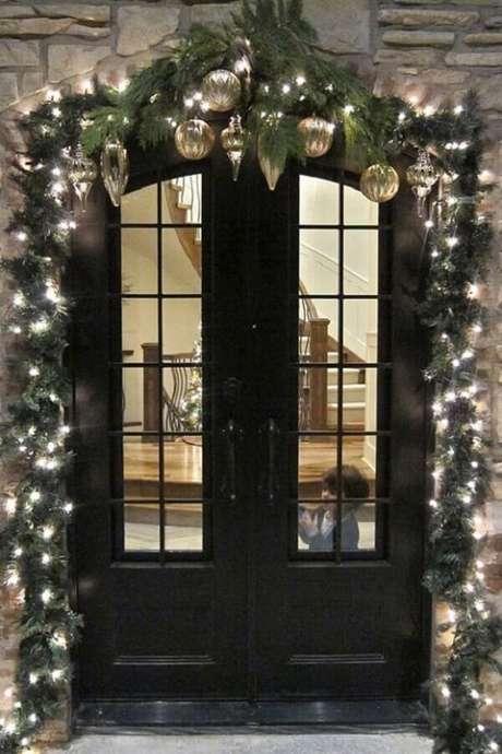 44. Luzes de natal para área externa decorada com enfeites dourados e festão verde – Foto: Divian Arts