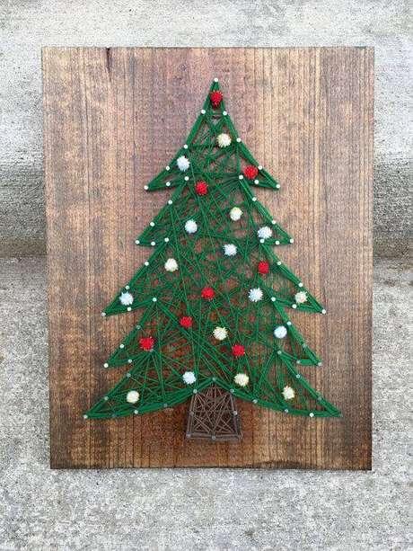 45- Artesanato de Natal feito com linhas e madeira formando uma linda arvore de natal