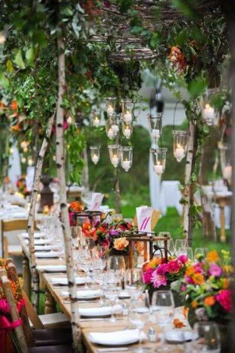 52. Festa externa com tema jardim encantado e mesas longas com decorações de flores e folhas. Foto de Pinterest