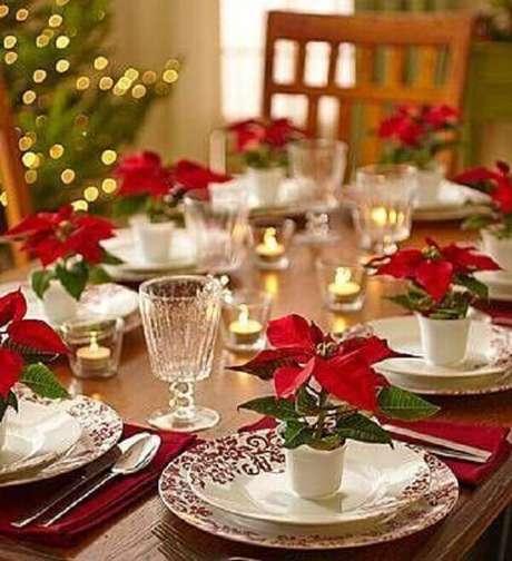12- Sobre os pratos da mesa da ceia foram utilizados pequenos vasos com flor de natal artificial. Fonte: Pinterest