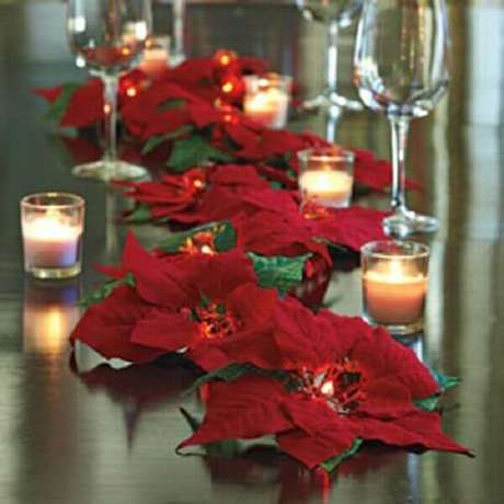 34- O centro de mesa foi elaborado com diversas velas e muitos arranjos de flor de natal. Fonte: Paula Lorentz