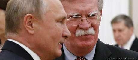 A pedido de Trump, John Bolton (dir.) convidou Vladimir Putin (esq.) para visitar os EUA