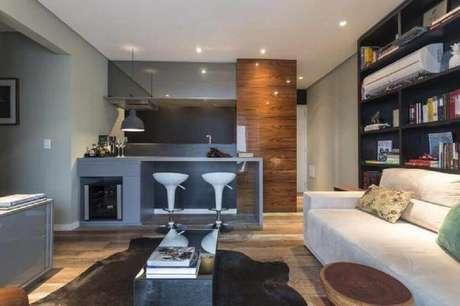 13. Decoração com parede de nichos e banquetas brancas para cozinha integrada com sala de estar – Foto: The Holk
