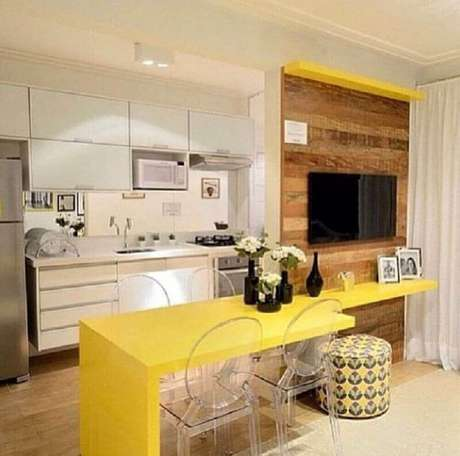 15. Decoração com bancada amarela e cadeiras de acrílico transparente para cozinha americana com sala de estar integrada – Foto: The Holk