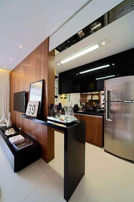 17. Decoração simples com bancada preta para cozinha americana com sala integrada – Foto: Pikby