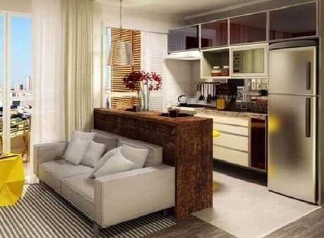 20. Cozinha americana com sala de estar decorada com sofá cinza e bancada de madeira – Foto: Webcomunica