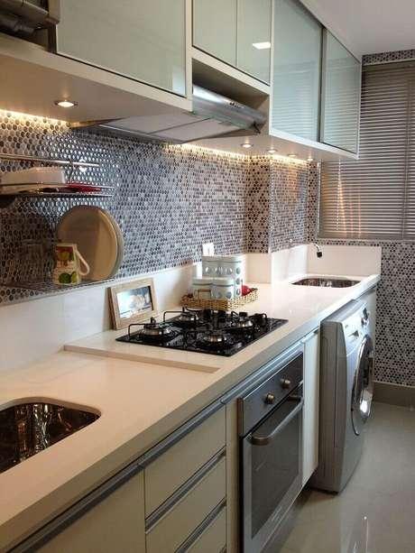 26. Cozinha com área de serviço decorada com pastilhas e armários planejados – Foto: Eunice Muniz