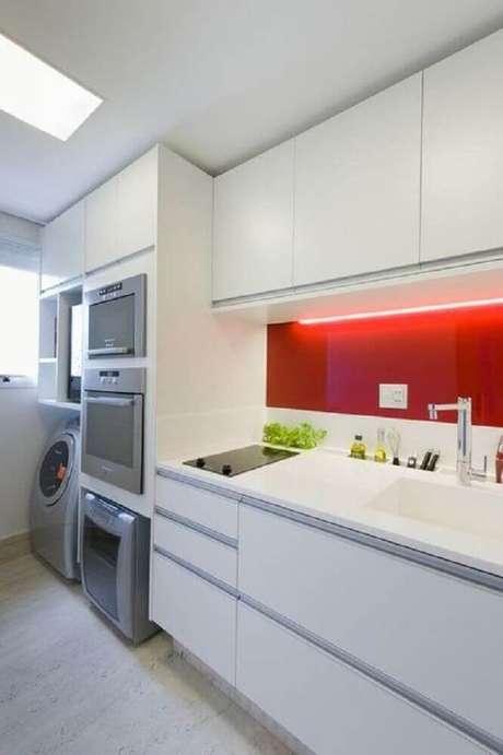 11. Decoração clean com parede vermelha e armários brancos para cozinha com área de serviço – Foto: Vazlon Brasil