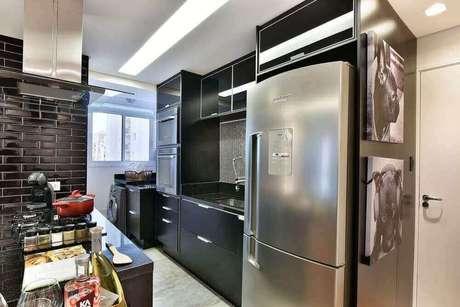 32. Os armários pretos também podem ser usados na cozinha com área de serviço pequena, mas para isso invista em um bom projeto de iluminação – Foto: Tetriz Arquitetura e Interiores