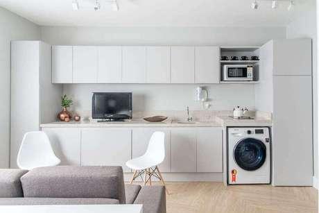 34. Decoração com armários planejados brancos para cozinha com área de serviço e sala de estar integrada – Foto: Renata Romeiro