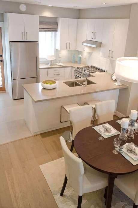 35. Decoração clean para cozinha integrada com sala de jantar com cadeiras brancas e mesa de madeira – Foto: Mi casa revista