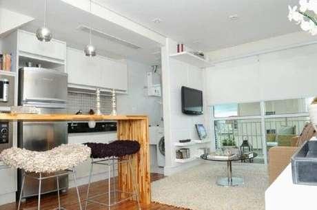 38. Decoração simples para cozinha integrada com sala de estar com bancada de madeira e armários brancos – Foto: Pinterest