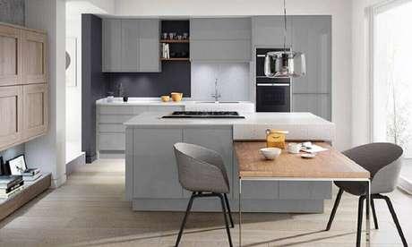 42. Decoração moderna em tons de cinza para cozinha integrada com sala de jantar com mesa acoplada a ilha – Foto: Home Care Exteriors