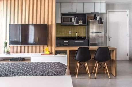 48. Decoração com bancada de madeira e cadeiras eames preta para cozinha americana com sala de estar – Foto: Danyela Corrêa