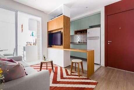 52. Decoração simples para cozinha americana para sala de estar com tapete vermelho e branco e bancada com painel de madeira – Foto: Pinterest