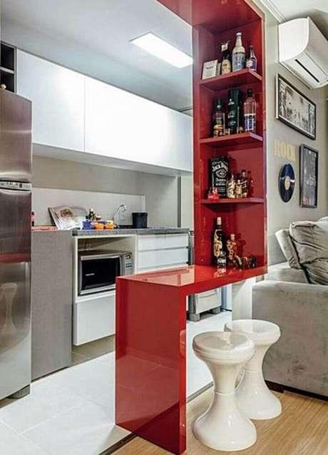 53. Decoração simples para cozinha americana com sala de estar com bancada e nichos vermelhos – Foto: Zozu