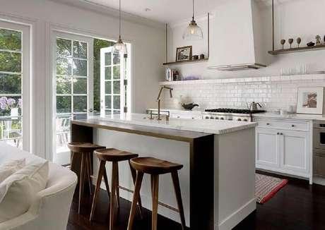 32. As banquetas de madeira para cozinha com decoração clean podem trazer sensação de conforto ao espaço