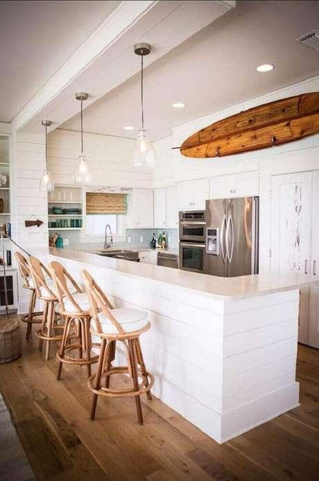 62. Decoração com banquetas para cozinha americana com pendentes sobre a bancada e prancha de madeira – Foto: Tuvalu Home