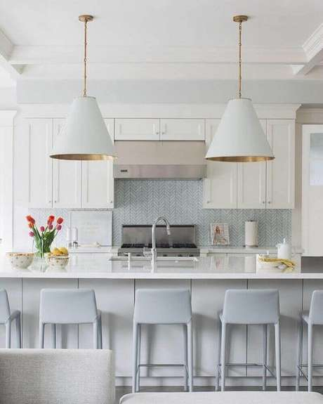 66. Decoração clean com banquetas para cozinha toda branca com grandes pendentes sobre bancada – Foto: Adriana Scartaris