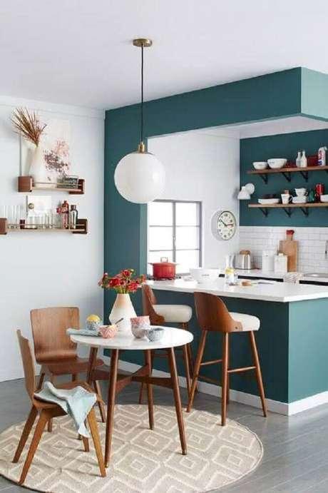 20. Aqui a cozinha compacta recebeu um modelo banqueta alta para cozinha com estrutura de madeira e assento branco