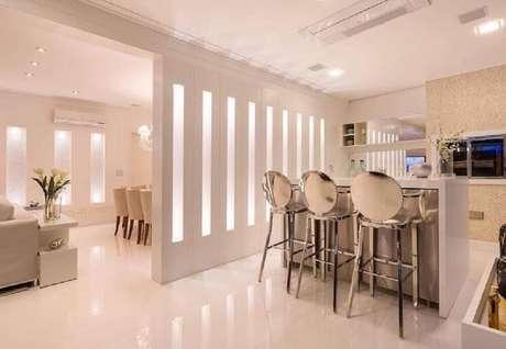 6. Decoração clean com banqueta alta para cozinha com material espelhado trazendo bastante modernidade ao ambiente.