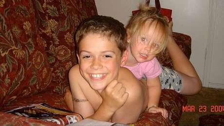 Paris, aos 10 anos, sorri e brinca com a irmã, Ella, então com dois anos de idade