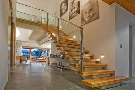 37. O acesso ao mezanino tem escadas de piso de madeira e guarda corpo em inox e vidro