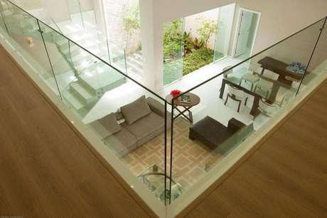 27. Ambiente de passagem para outros cômodos com piso elegante e vidro de proteção
