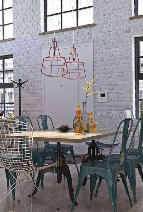 35. Decoração com estilo industrial para sala de jantar com pendente aramado vermelho e parede de tijolinho branco – Foto: Pinterest