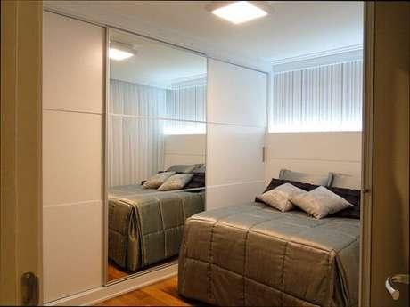 65- O guarda-roupa com porta de espelho decora o quarto em estilo moderno. Fonte: Casa e Festa
