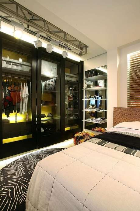 40. Este guarda-roupa planejado com portas de vidro e metal preto dá uma aparência muito moderna ao projeto de Mari Ani Oglouyan