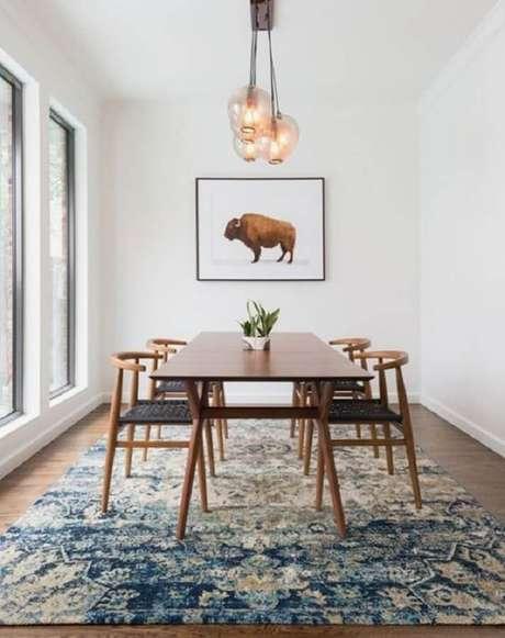 38. Decoração clean para sala de jantar com luminárias de teto e grande tapete azul – Foto: Pinterest