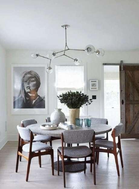 42. Decoração minimalista para sala de jantar com mesa redonda e luminária de teto diferente – Foto: Pinterest