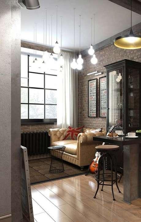 11. A parede de tijolinho à vista junto com as luminárias de teto para sala de estar estilo pendente se tornaram o grande destaque do ambiente – Foto: Mauricio Gebara Arquitetura