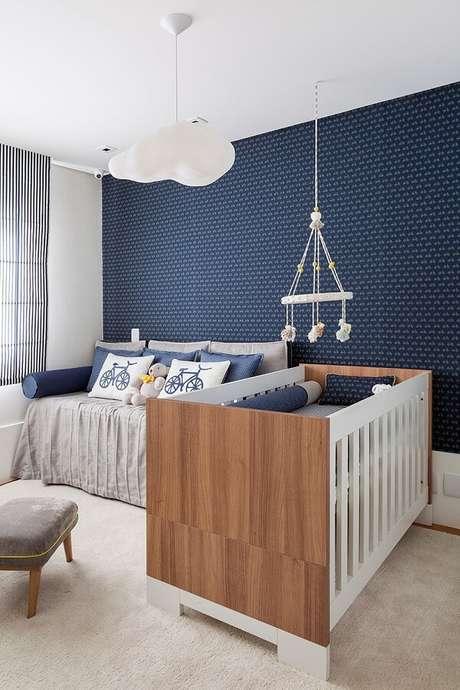 66. Quarto de bebê decorado em tons de azul com papel de parede e luminária de teto em formato de nuvem – Foto: Homerly