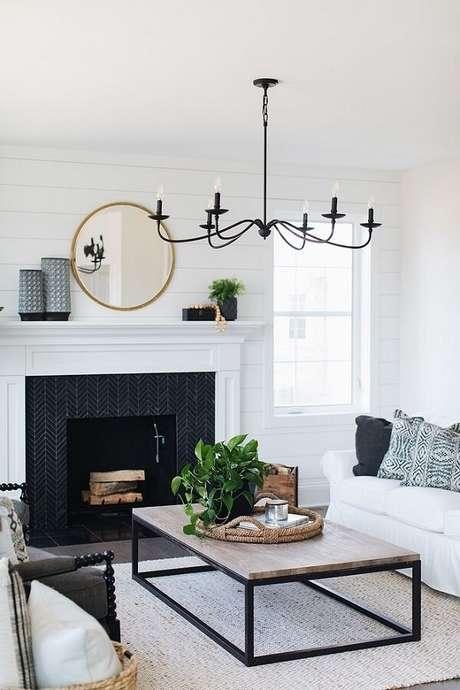 68. Sala de estar decorada com lareira, sofá branco e luminária de teto – Foto: HomeBunch
