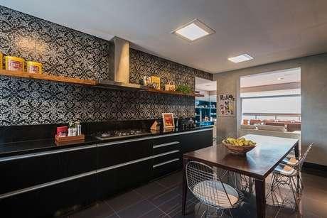 29. A decoração de cozinha preta recebeu uma parede toda revestida com ladrinho hidráulico garantindo mais charme ao ambiente