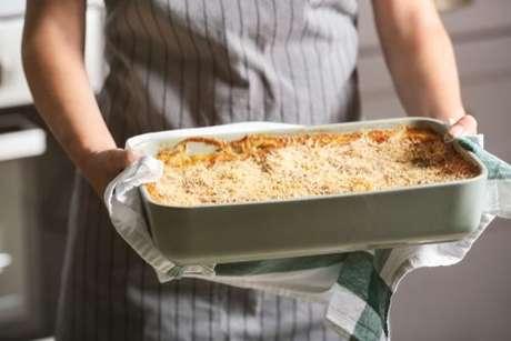 Cozinheira segurando travessa com lasanha de bacalhau