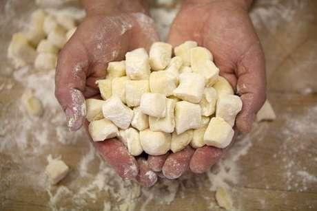 Quadradinhos de nhoque de mandioquinha nas mãos de um chef